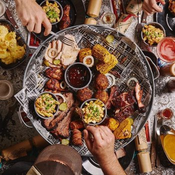 The Christmas Feast is a bin lid filled with our best low and slow meats, plus festive additions. Enquiries now open for groups of 4+ in December. Link in bio.